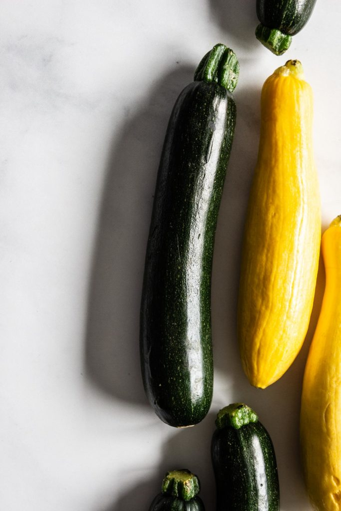 Green and yellow zucchini squash on a white countertop.