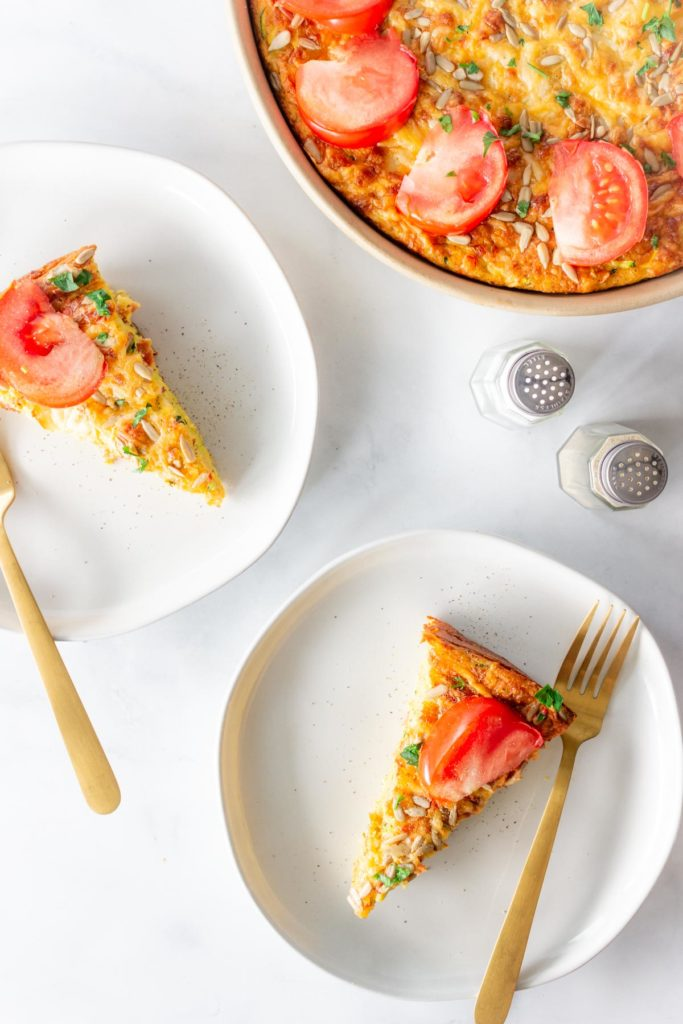 Two slices of crustless zucchini bacon quiche are served on white plates with gold forks.