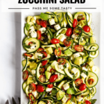 A beautiful spiralized zucchini salad with grape tomatoes, feta, and avocado tossed together on a square white serving dish.