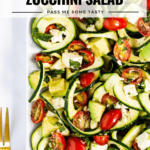 A zucchini salad with tomatoes, basil, and feta . Two gold forks rest nearby.