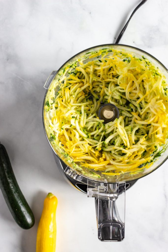 Green and yellow zucchini grated effortlessly in a food processor.