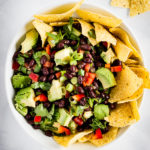A bowl of avocado black bean salsa with tortilla chips tucked into the sides and scattered on the countertop.