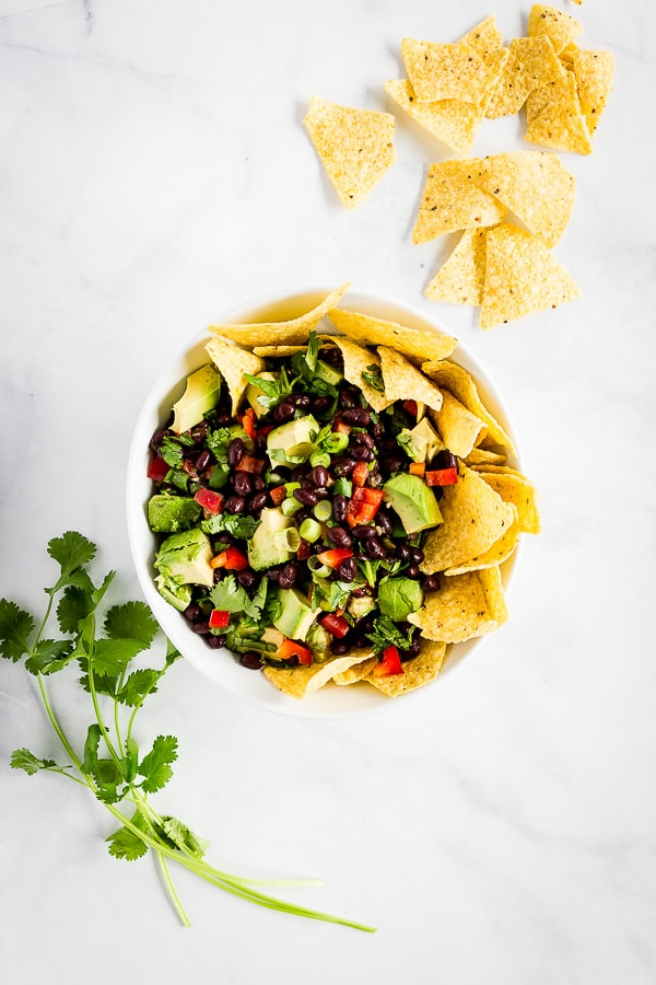 A bowl of avocado black bean salsa served with tortilla chips. A few sprigs of cilantro sit nearby.
