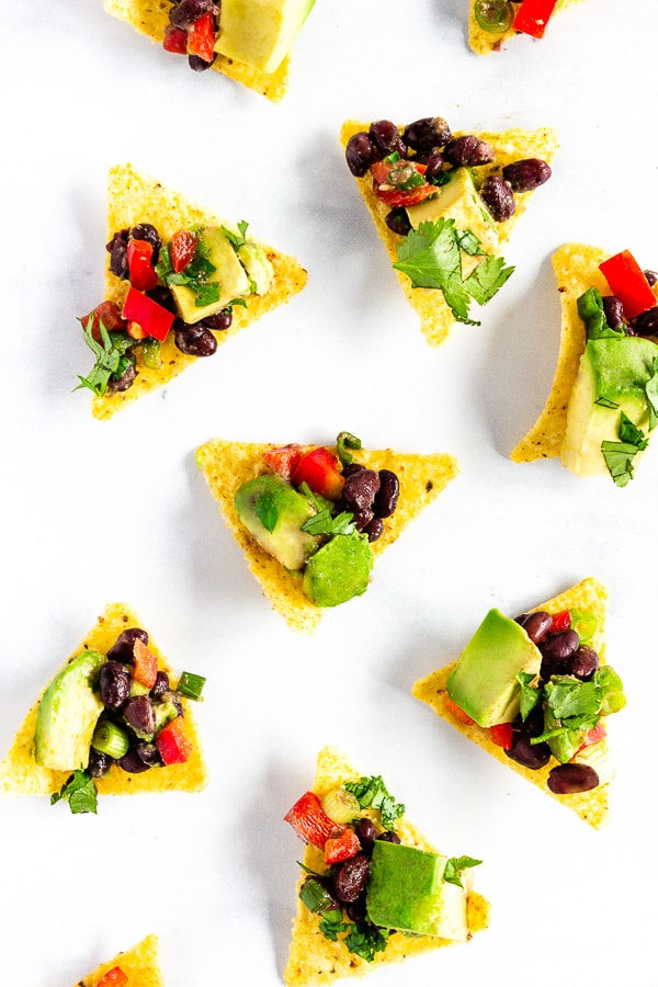 Tortilla chips topped with avocado black bean salsa sit scattered on a white countertop.
