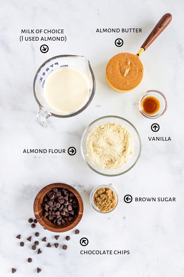 Ingredients for chocolate chip cookie dough popsicles are laid futon a marble countertop: milk, almond butter, vanilla, almond flour, brown sugar, and chocolate chips.