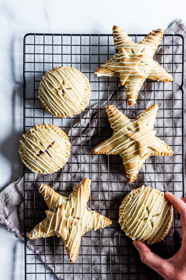 Circle and star shaped gluten-free raspberry hand pies with white chocolate drizzle rest on a cooling rack. a hand it reaching forth to grab one.
