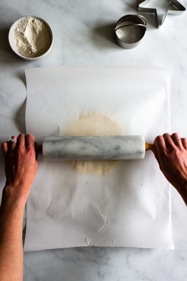 A second piece of parchment is placed on top of the hand pie dough. A marble rolling pin is rolling out the dough.