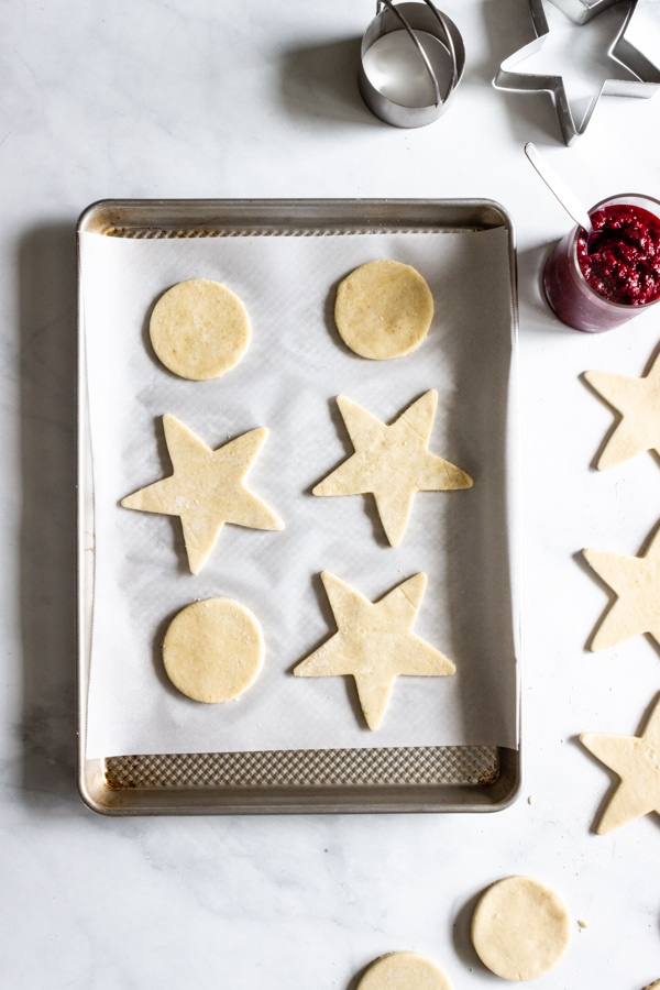 Circles and stars are cut-out and placed on a parchment lined baking sheet. Homemade raspberry jam sits nearby in a jar.
