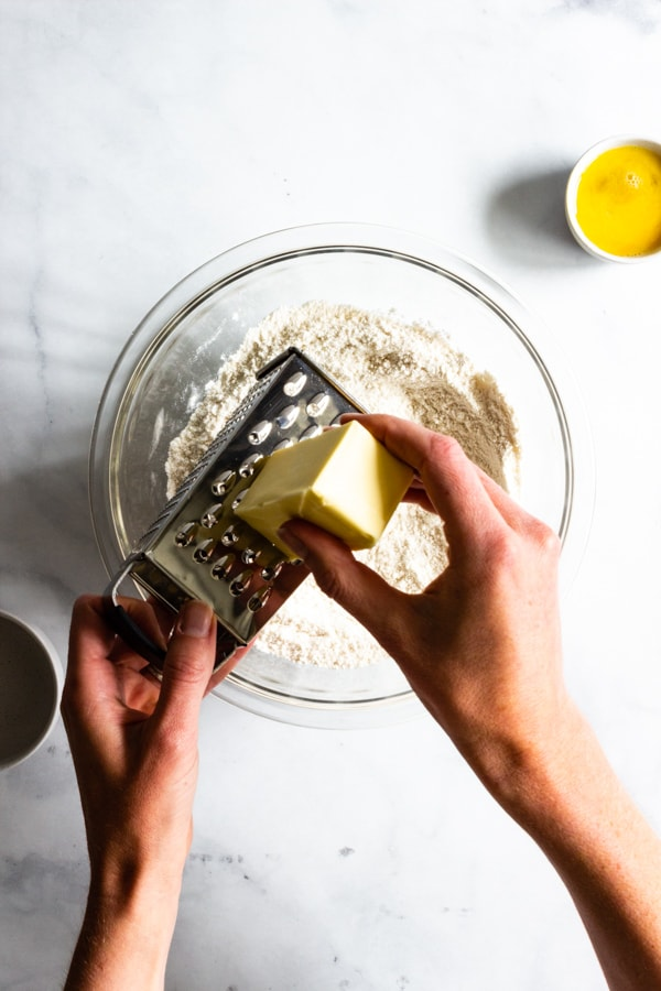 Grating frozen unsalted butter into the dry hand pie dough ingredients.