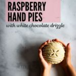 Two small hands of a child are outstretched holding a gluten-free raspberry hand pie with white chocolate drizzle.