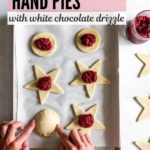 Two hands are gently pressing dough to the top of a raspberry hand pie.