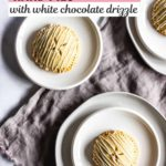 Three round hand pies with white chocolate drizzle sit on white plates.