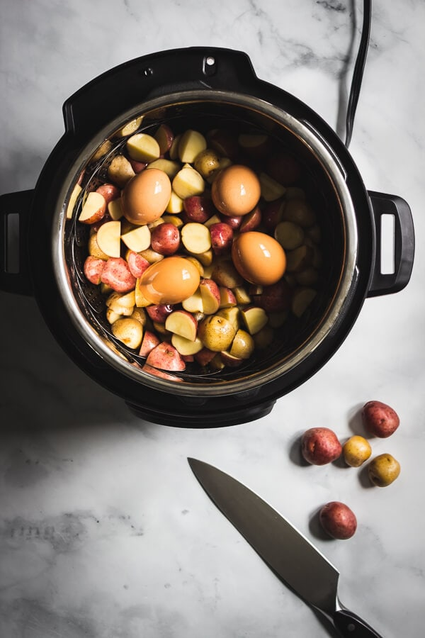 Halved baby potatoes and eggs are placed in an Instant Pot ready to be cooked.