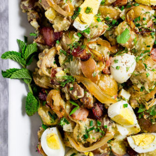 A close-up of view of potato salad with caramelized onions, slices of hard boiled eggs, chunks of salty crispy bacon, and fresh herbs.