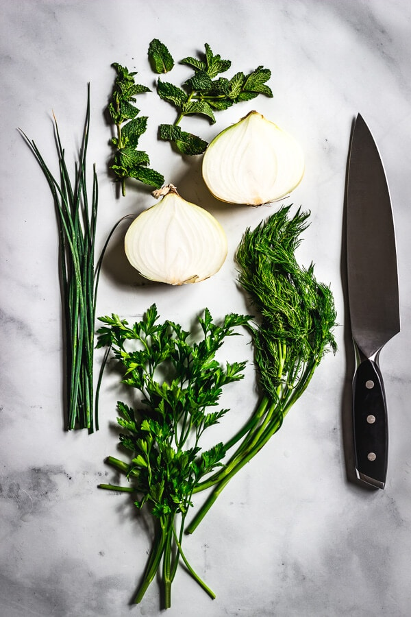 Fresh dill, flat leaf Italian parsley, mint, dill, and a halved sweet onion sit on a marble countertop. A chef's knife sits alongside.