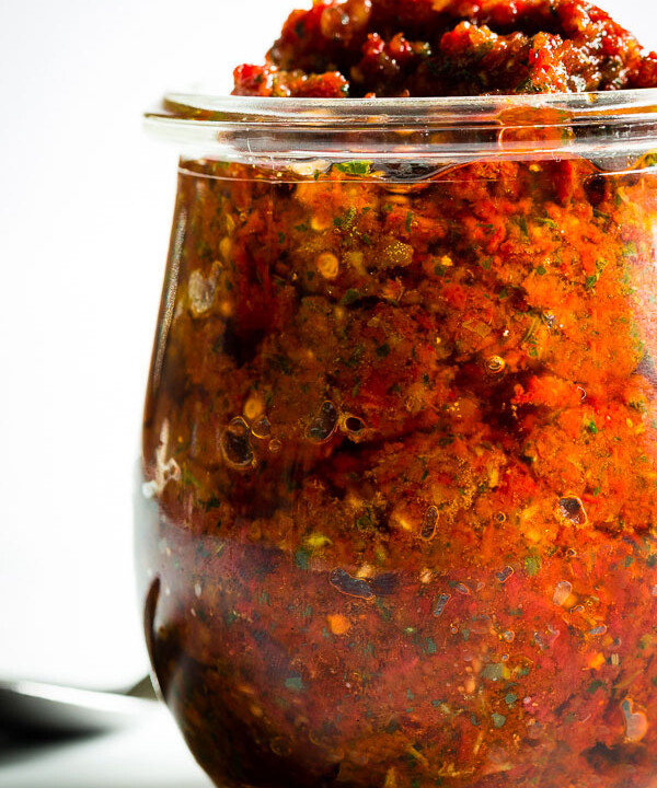 A close-up of a beautiful jar of bright-red sun-dried tomato pesto.