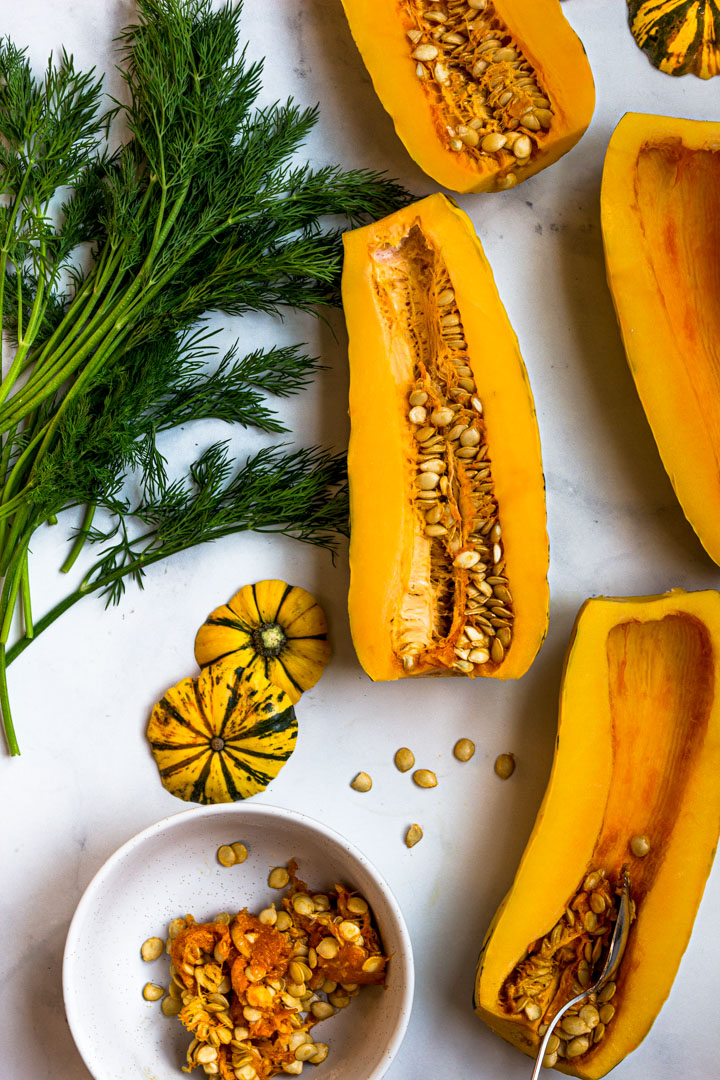The delicata squash are sliced in half lengthwise and the seeds are being removed.