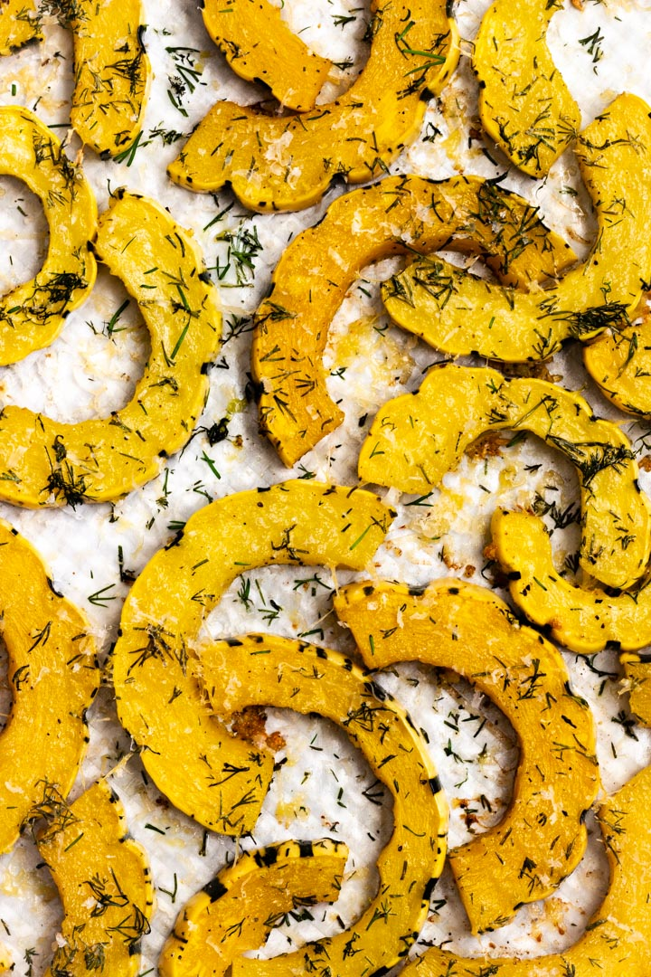 Roasted delicata squash with dill and finely grated parmesan on a pan.