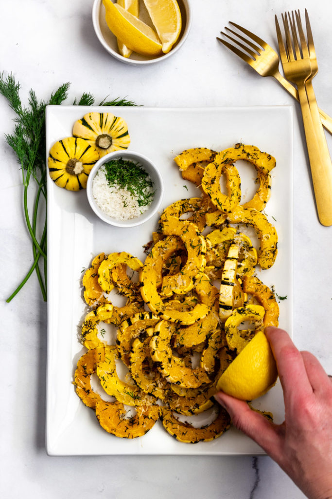 A lemon wedge is being squeezed over the roasted delicata squash.