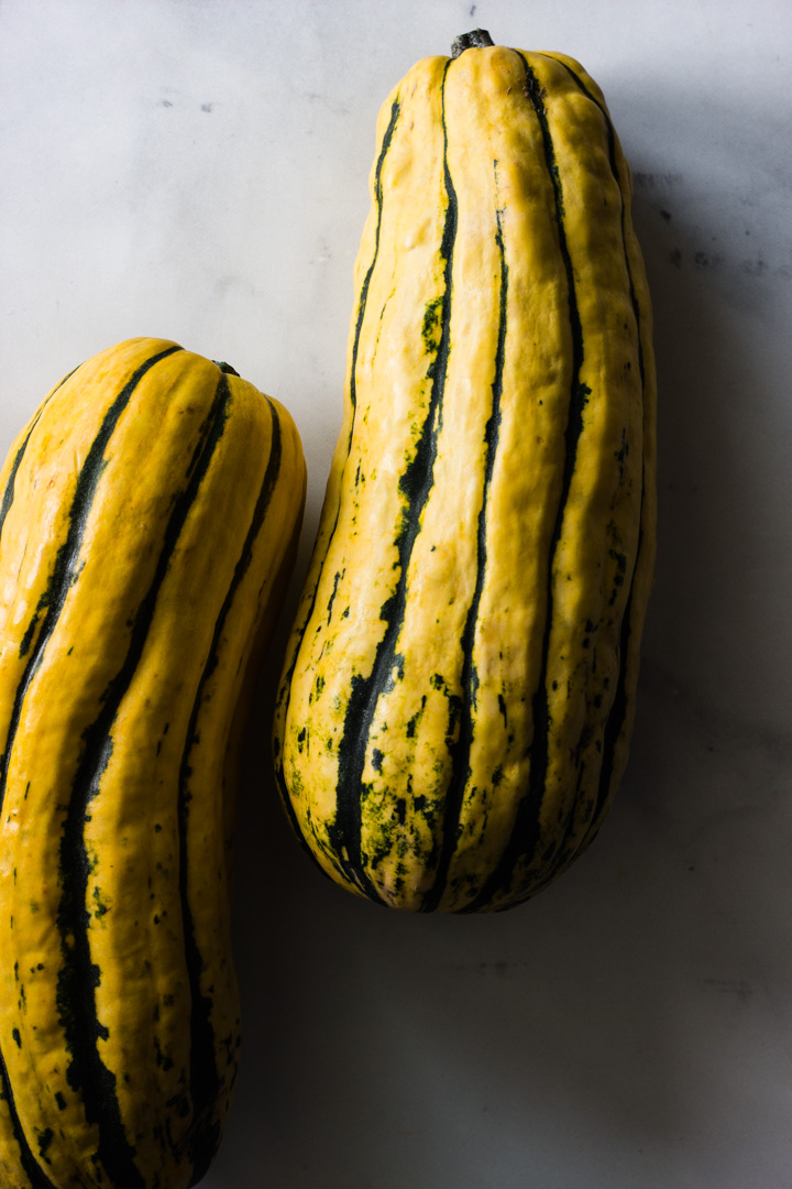Two delicata squash resting on a marble countertop.