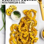 A white platter with roasted delicata squash with Parmesan and dill. A small dish of lemon wedges are served nearby.