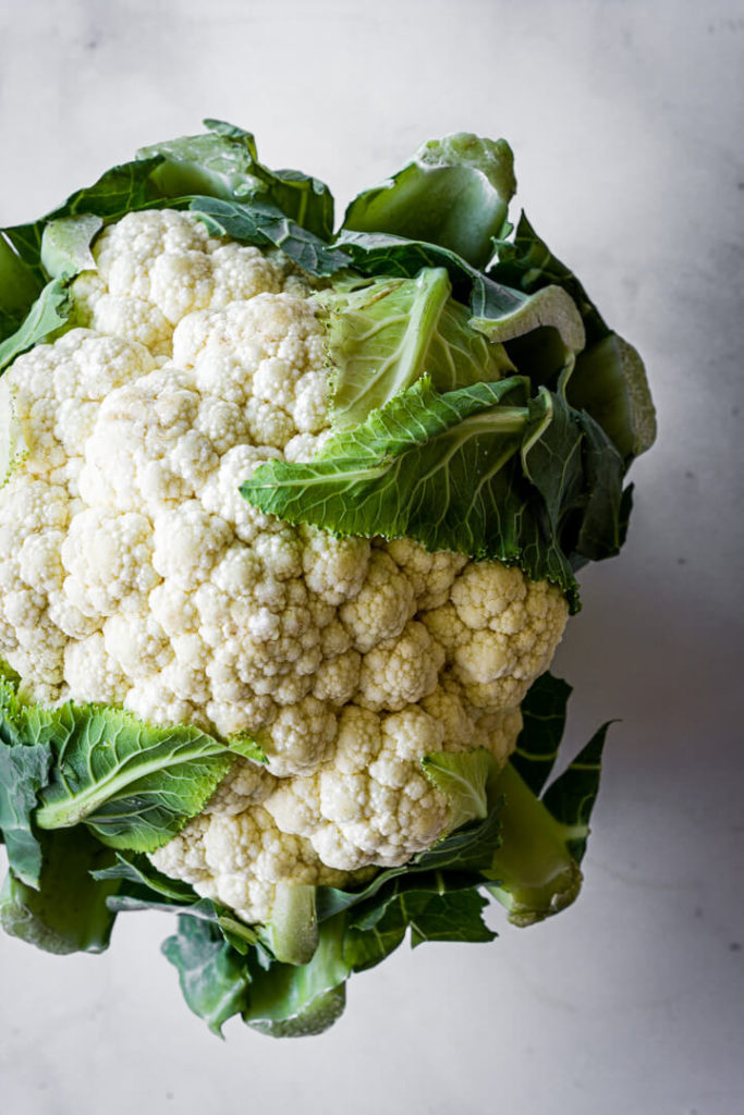 A head of cauliflower sitting on a marble countertop.