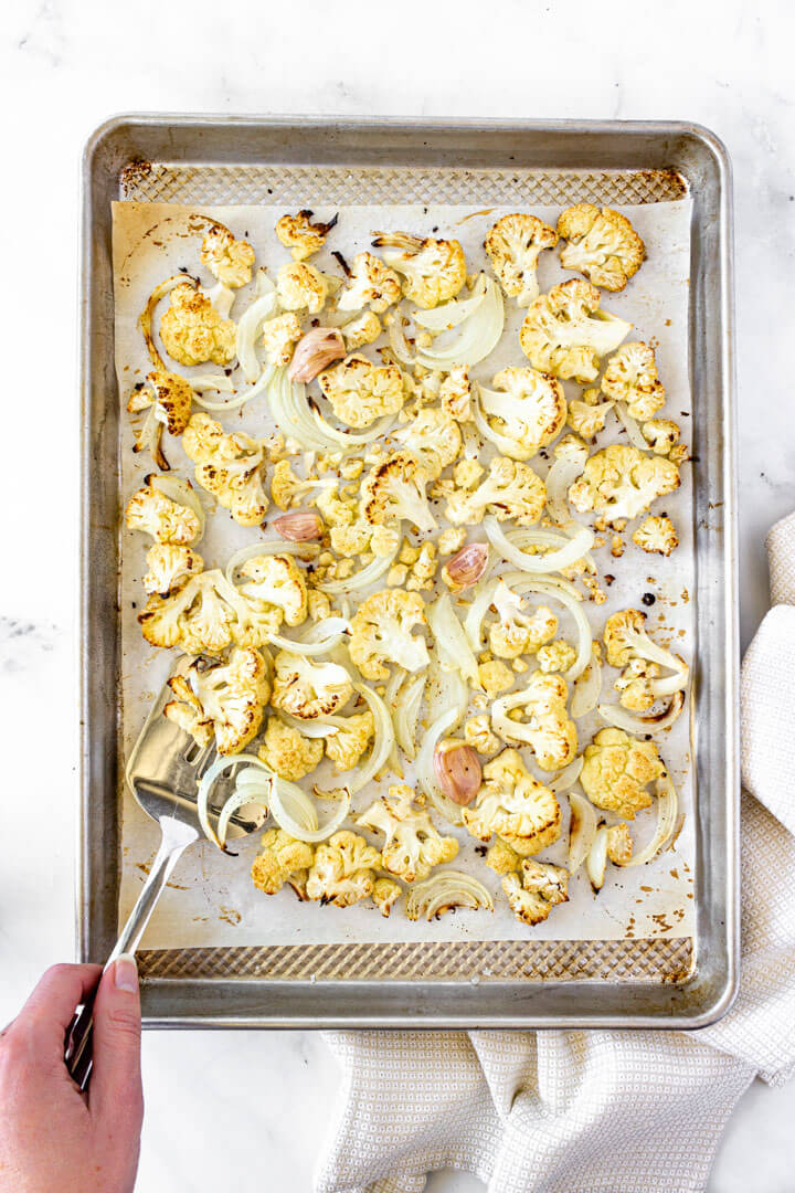 Cauliflower florets, sliced onions, and garlic are roasted.