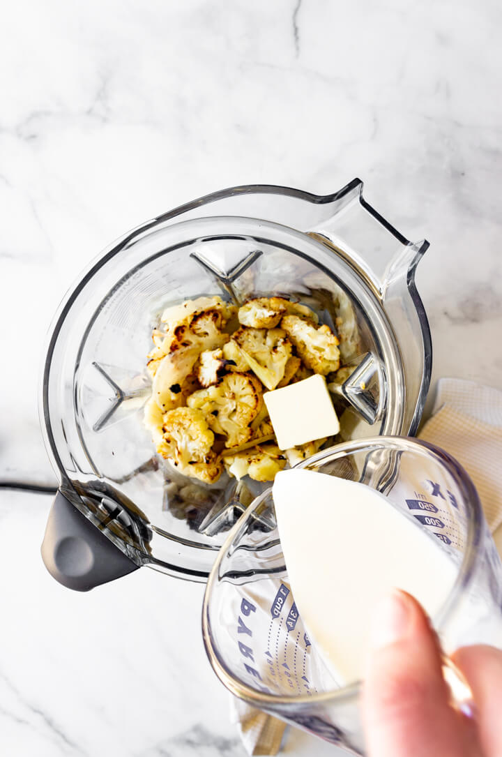 Roasted cauliflower, onions, and garlic are placed in a high speed blender. Butter and heavy whipping cream is added.