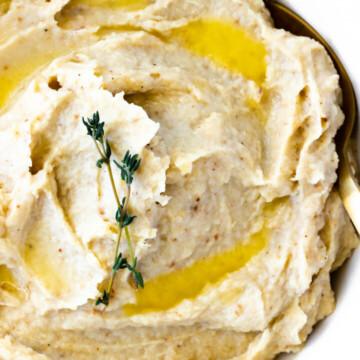 A close-up view of creamy roasted mashed garlic cauliflower.