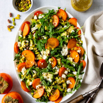 Beautiful persimmon arugula salad topped with chopped pistachios, feta, and a simple lemon vinaigrette.