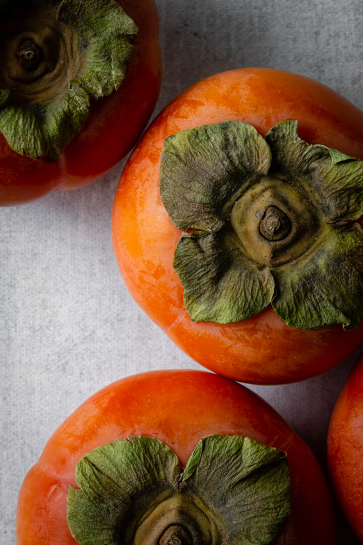 Bright orange-red persimmons sitting on a gray countertop.