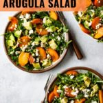 Two plates of persimmon arugula salad topped with crumbled feta, chopped pistachios, and a lemon vinaigrette.