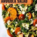 Quartered persimmons are tucked into a pile of arugula and topped with crumbled feta and chopped pistachios.