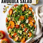 A beautiful persimmon arugula salad topped with chopped pistachios, feta, and a simple lemon vinaigrette.