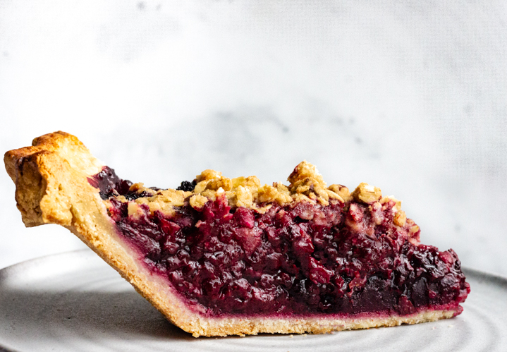 A side view of a slice of blackberry bourbon pie with streusel topping.