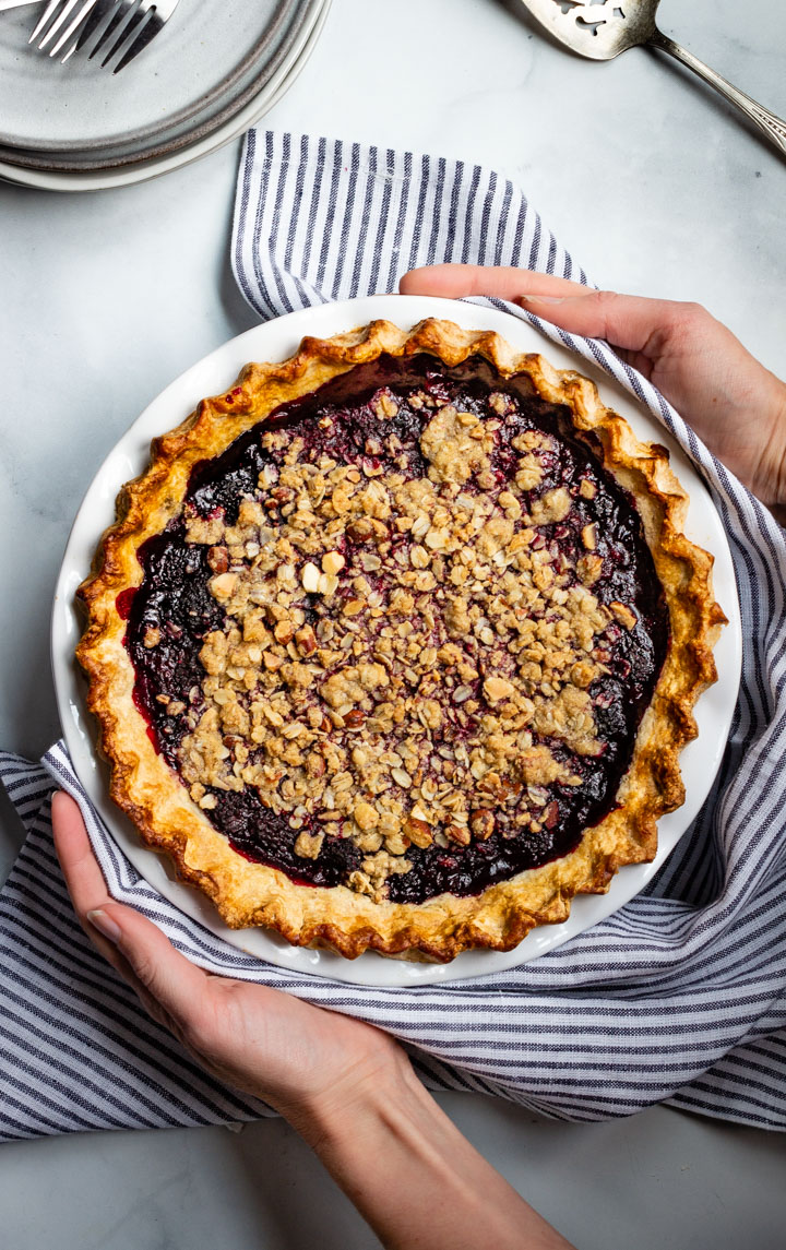 Two hands holding a Gluten-Free Blackberry Bourbon Pie with a crumble topping and flaky, golden crust.