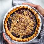 Two hands holding a Gluten-Free Blackberry Bourbon Pie