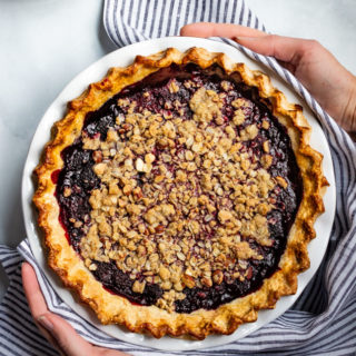 Two hands holding a Gluten-Free Blackberry Bourbon Pie
