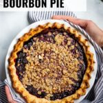 Two hands holding an Oregon Marionberry blackberry pie with a crumble topping and a golden, flaky, gluten-free crust.