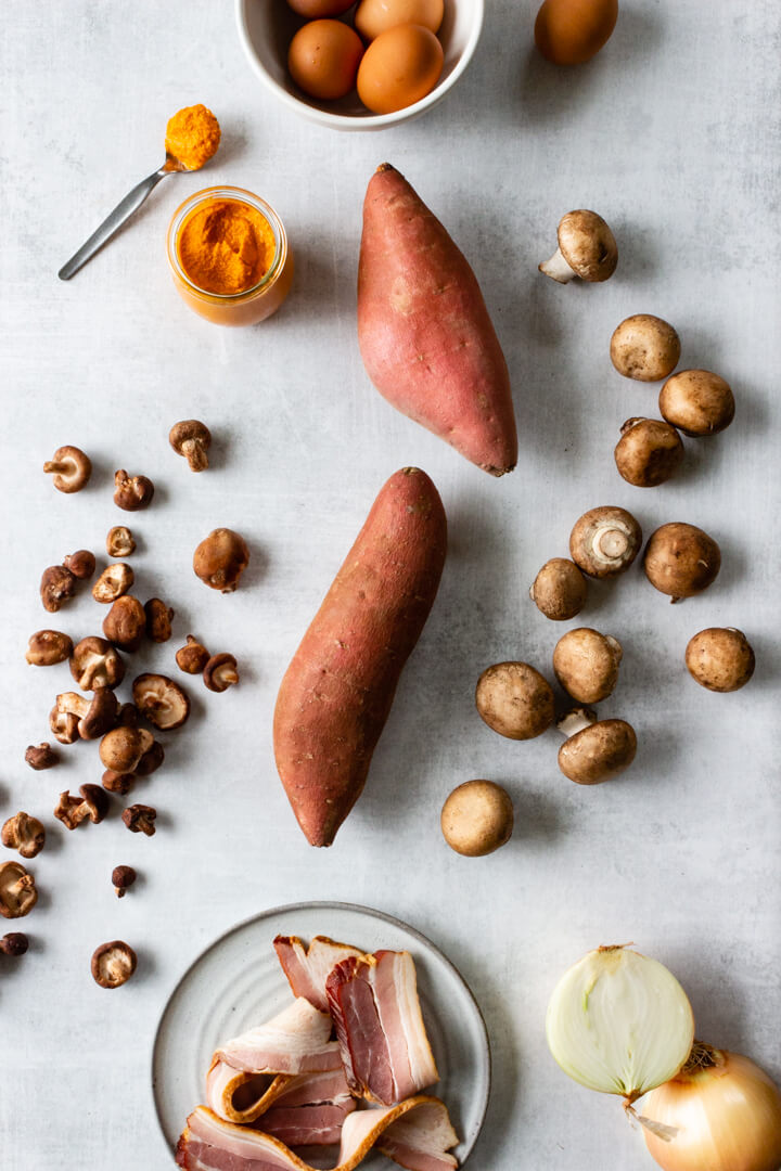 Ingredients for a hearty sheet pan sweet potato hash breakfast are laid out on a counter.