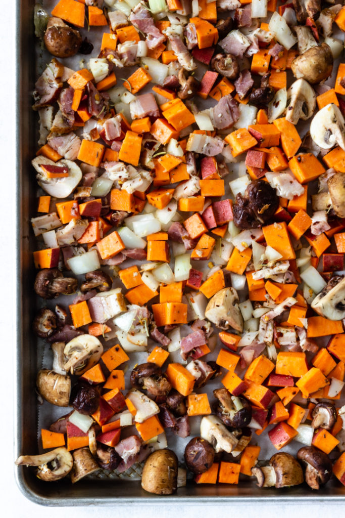 All of the ingredients are spread out on a sheet pan and are ready to be placed in the oven for roasting.