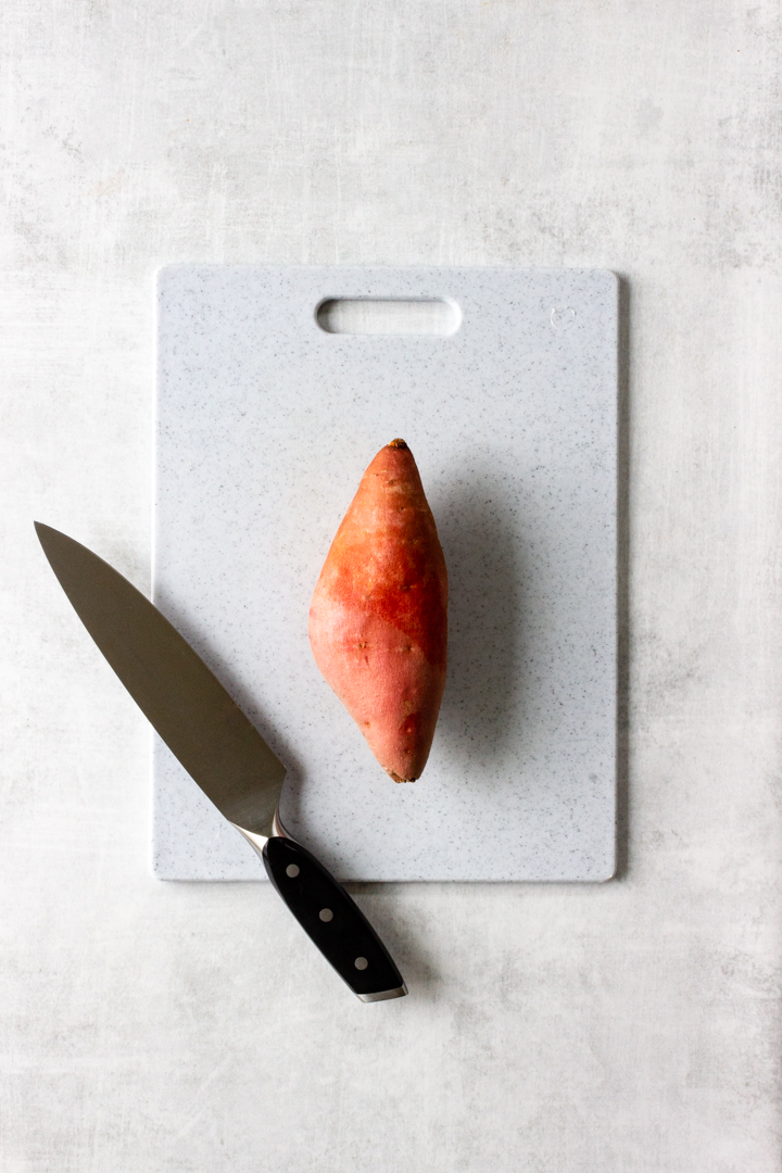A sweet potato is resting on a cutting board with a knife.