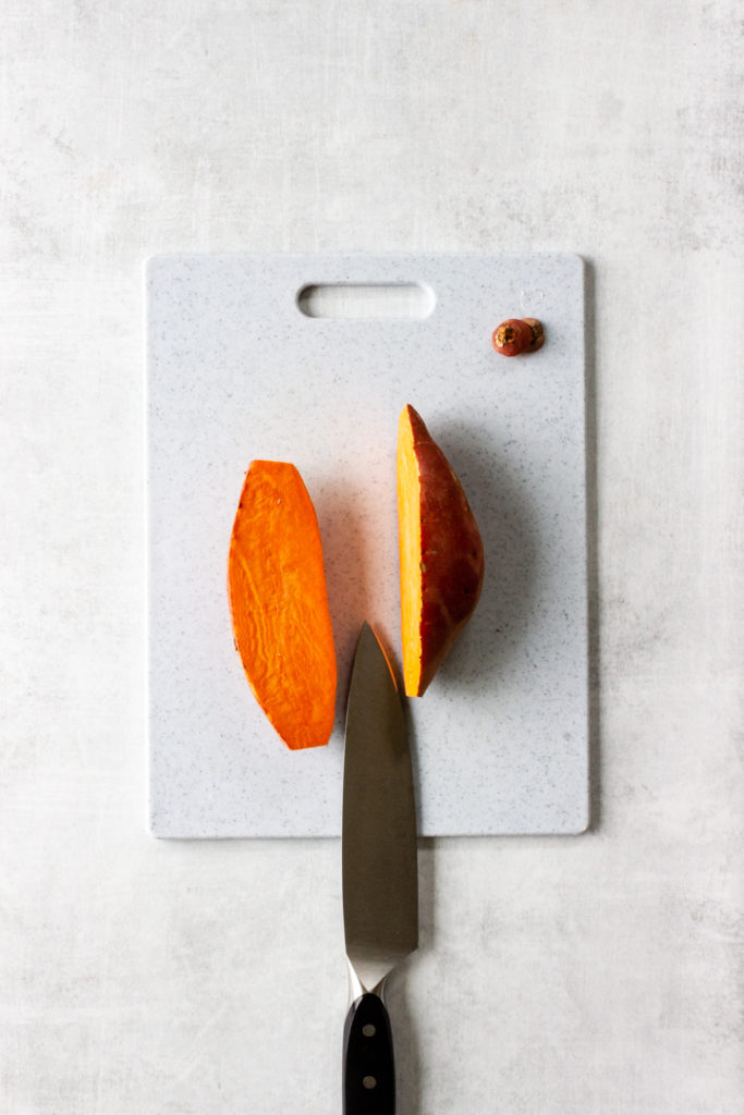 A sweet potato has its ends cut off and is then cut in half lengthwise.