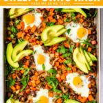 A sheet pan of roasted vegetables topped with baked eggs, avocado slices, and served over spinach.
