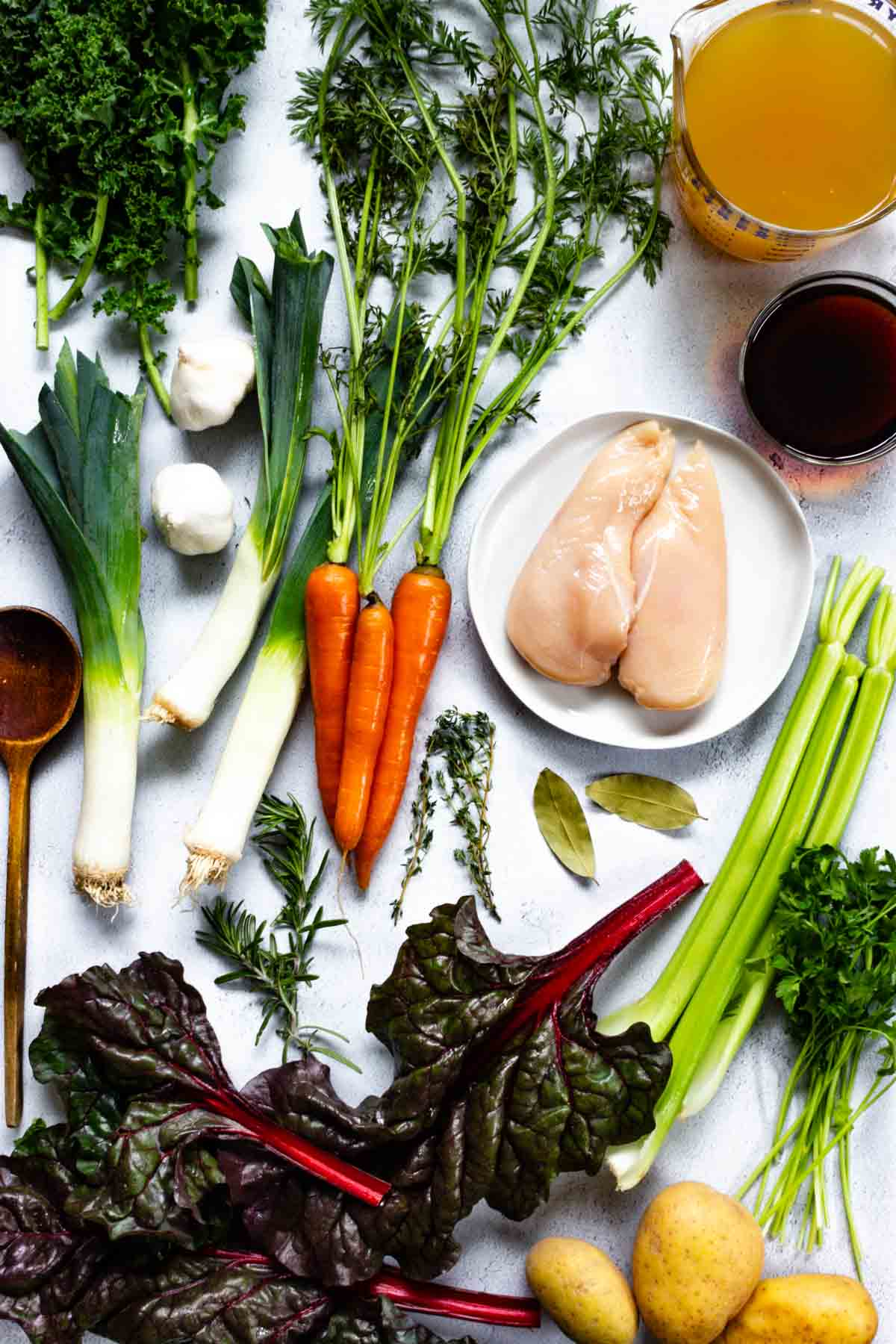 Ingredients for gluten-free flu fighting chicken soup are all laid out on a counter.