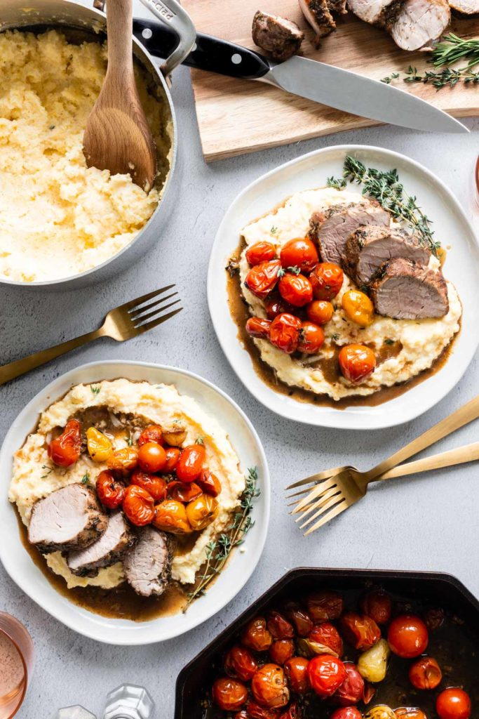 A table set with a pot of creamy polenta, a cutting board with sliced herb-crusted pork tenderloin, a skillet of roasted cherry tomatoes, and two plates with a serving of each.