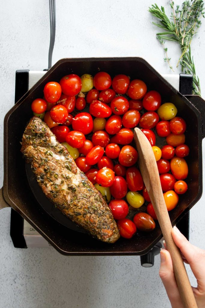 A cast iron skillet with herb-crusted pork tenderloin and garlic roasted cherry tomatoes.