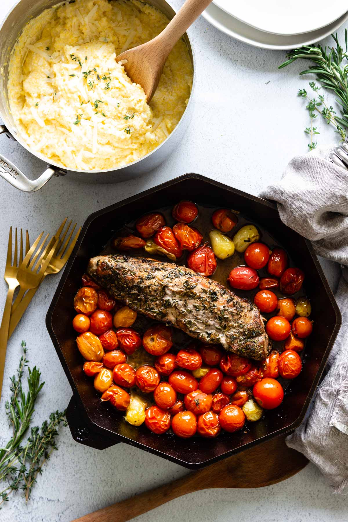 A cast iron skillet with herb-crusted pork tenderloin, garlic roasted cherry tomatoes, and a pot of creamy polenta nearby.