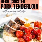 A plate with several slices of herb-crusted pork tenderloin served over creamy polenta and roasted cherry tomatoes.