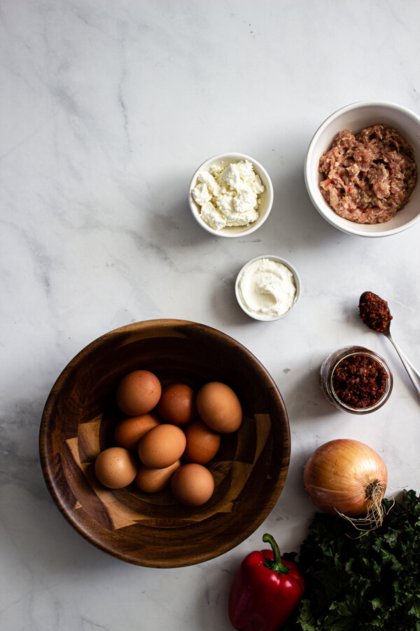 Ingredients for a baked frittata with sausage, kale, and sun-dried tomato pesto are laid out on a marble countertop.
